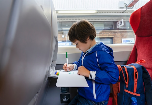 Portrait kid traveling by the train, child drawing cartoon on white paper sitting by the window. little boy in a high speed express train on family vacation