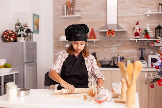 Portrait of kid wearing apron preparing homemade dough using rolling pin