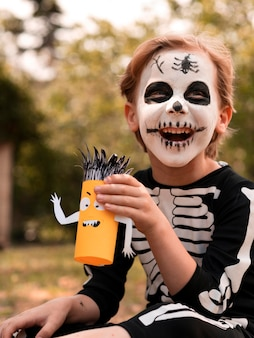 Portrait of kid with face painted for halloween