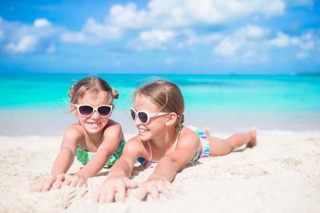 Portrait of kids lying on warm white sand