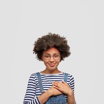 Portrait of kind hearted african american female in fashionable overalls, keeps hands on chest, shows her kindness and sympathy, has pleased cheerful expression, isolated over white wall