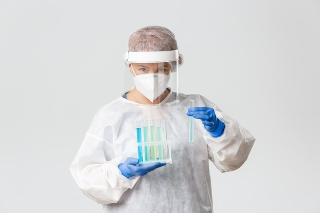 Portrait of lab tech, scientist or doctor in personal protective equipment holding test-tubes with vaccine samples, searching for cure