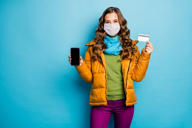 Portrait of lady hold telephone plastic card wear safety mask remote isolated blue color background