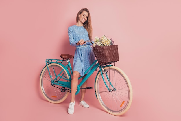 Portrait of lady riding a bike deliver flowers in mini dress shoes on pink background