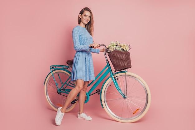 Portrait of lady riding a bike in mini dress footwear on pink background
