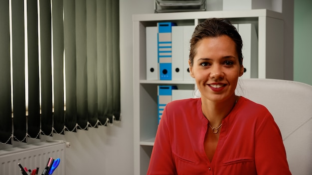 Portrait of lady smiling in front of camera in modern office room. slow motion of hispanic freelancer working in professional workplace in personal corporate company looking at webcam