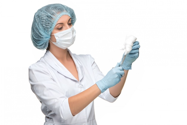 Portrait of lady surgeon holding surgical instrument over white background