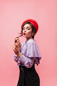 Portrait of lady wearing purple blouse, beret and pants. girl paints her lips on pink background.