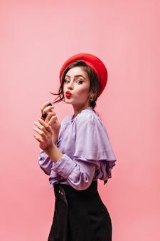 Ritratto di signora che indossa pantaloni, berretto e camicetta viola. la ragazza dipinge le sue labbra su sfondo rosa.