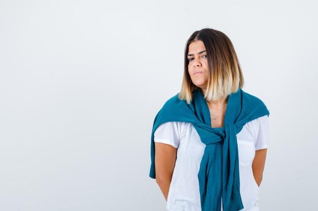 Ritratto di signora con maglione legato con le mani dietro la schiena in maglietta bianca e guardando fiducioso vista frontale