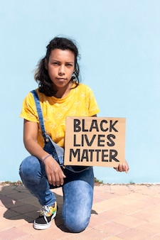Portrait of latin american woman with serious attitude holding a banner with slogan black lives matter