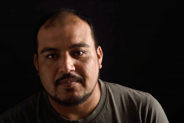 Portrait of a latin man on black background
