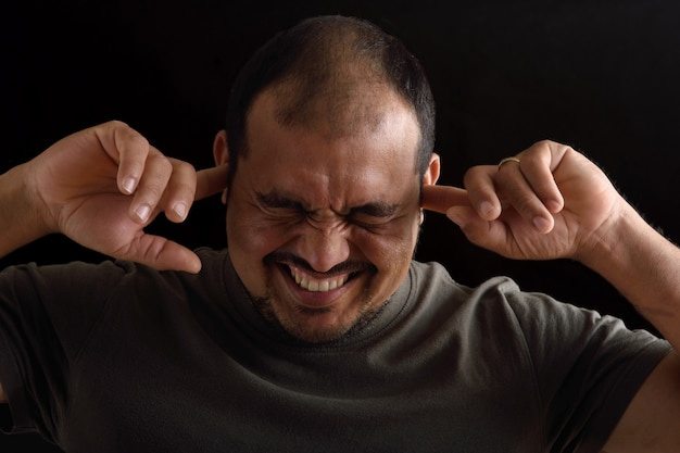 Portrait of a latin man with noise on black background