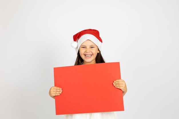 Portrait of laughing caucasian girl in white dress and santa claus hat holding red blank poster isol...