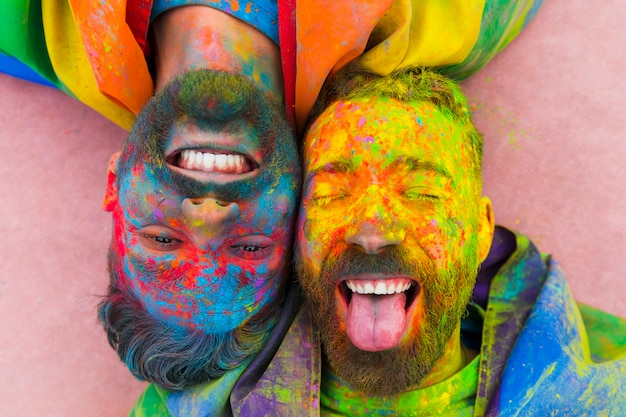 Portrait of laughing gay pair soiled in paint