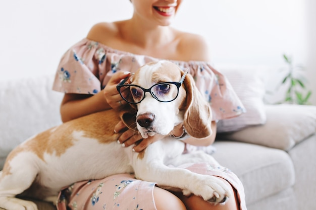 Portrait of laughing girl in pink dress with sad beagle dog in glasses on foreground