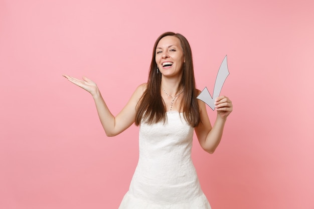 Portrait of laughing happy woman in white dress pointing hand aside, holding check mark,