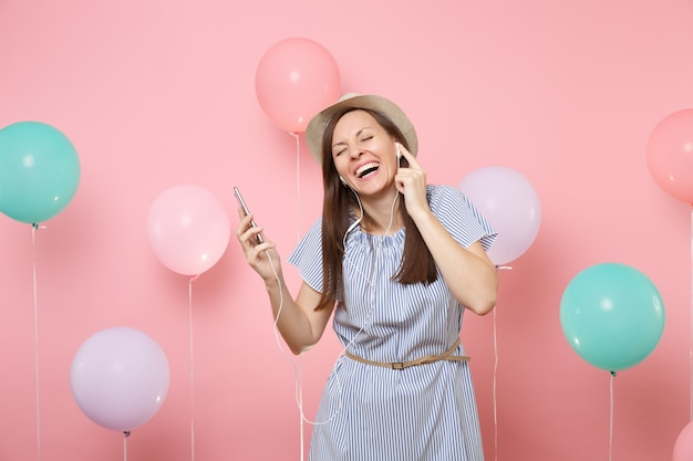 Portrait of laughing happy young woman in straw summer hat and blue dress with mobile phone and earphones listening music on pastel pink background with colorful air balloons. birthday holiday party.