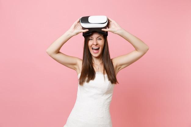 Ritratto di ridente donna gioiosa in abito bianco che tiene in mano le cuffie della realtà virtuale