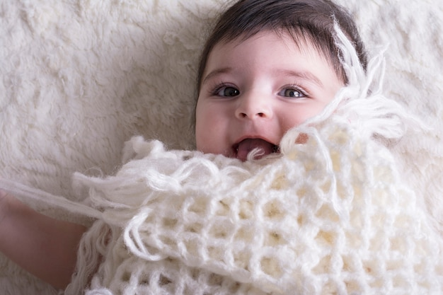 Portrait of laughing little baby girl under knitted cloth