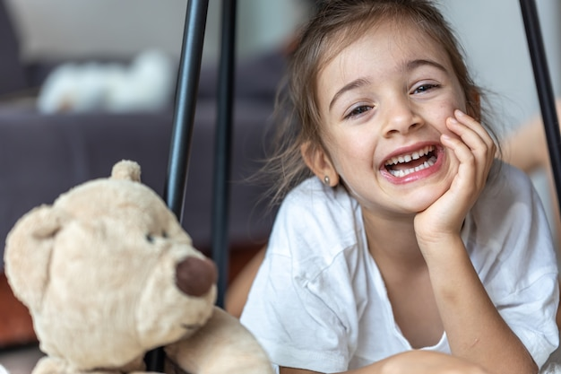 Portrait of a laughing little girl near a teddy bear at home.