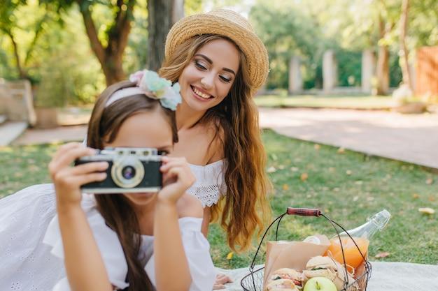Ritratto di ridere signora dai capelli lunghi in cappello con la fotocamera della holding della ragazza. foto all'aperto di giovane donna che si diverte al picnic e sua figlia seduta cesto besie con pasto.