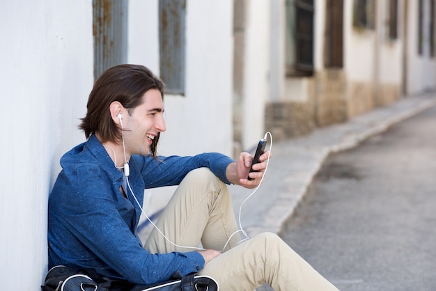 Portrait of laughing man sitting on city street with phone and bag