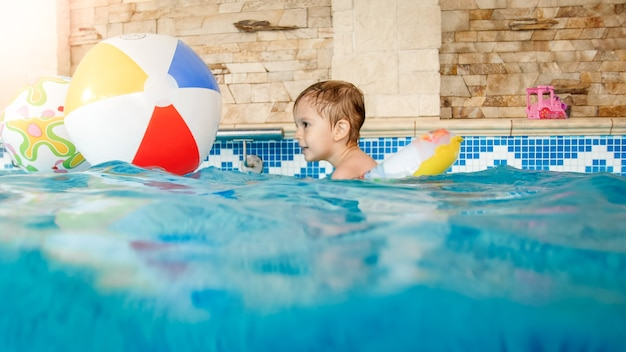 Portrait of laughing and smiling 3 years old little boy swimming with inflatable colorful ring and playing with beach ball in swimming pool