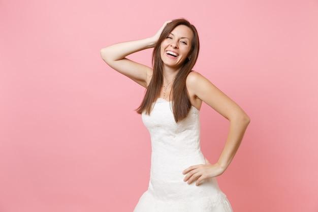 Ritratto di donna che ride in bellissimo abito bianco in piedi e tenendo la mano vicino alla testa