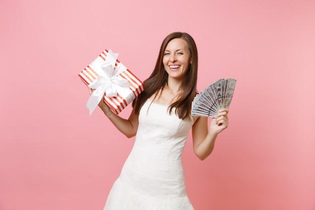 Il ritratto di una donna che ride in abito bianco tiene in mano un sacco di dollari, denaro contante, scatola rossa con regalo, regalo