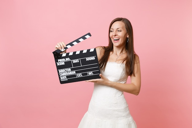 Portrait of laughing woman in white dress holding classic black film making clapperboard