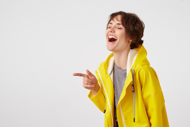 Portrait of laughing young happy cute short haired girl wears in yellow rain coat, broadly smiles, hears funny jokes, stands over white wall and points to copy space at the left.