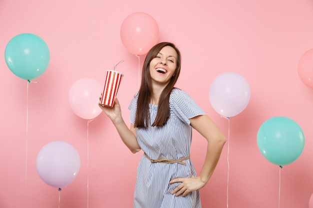 Portrait of laughing young pretty woman in blue dress holding plastic cup of cola or soda on pastel pink background with colorful air balloons. birthday holiday party, people sincere emotions concept.