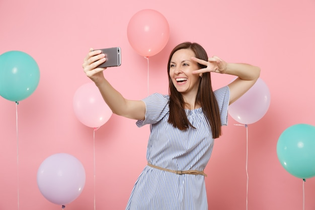Portrait of laughing young woman in blue dress doing selfie on mobile phone showing victory sign on pink background with colorful air balloons. birthday holiday party, people sincere emotions concept.