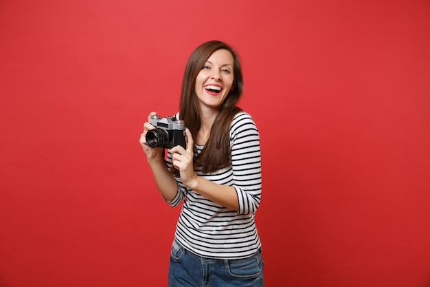 Portrait of laughing young woman in casual striped clothes holding retro vintage photo camera isolated on bright red wall background. people sincere emotions, lifestyle concept. mock up copy space.