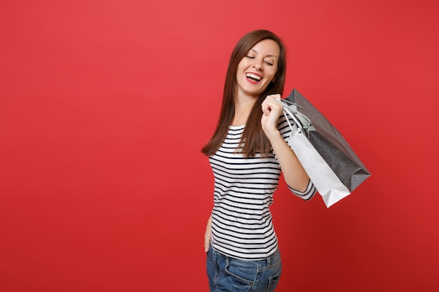 Portrait of laughing young woman looking back on packages bags with purchases after shopping in hands isolated on red wall background. people sincere emotions, lifestyle concept. mock up copy space.
