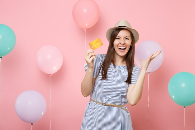 Portrait of laughing young woman in straw summer hat blue dress hold credit card spreading hands on pink background with colorful air balloons. birthday holiday party people sincere emotions concept.