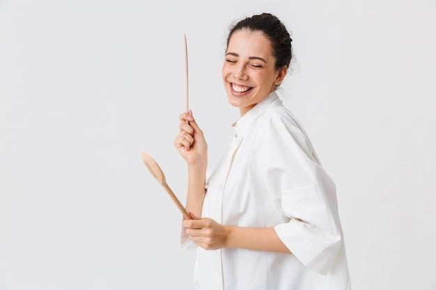 Portrait of a laughing young woman with kitchen utensils