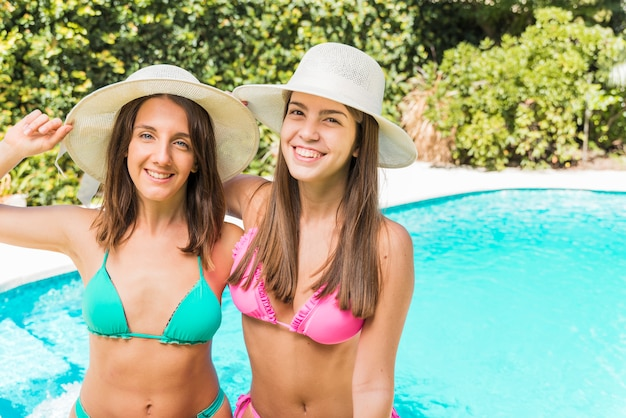 Portrait of laughing young women posing in hat near pool