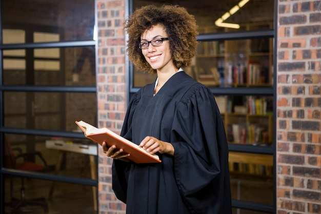 Portrait of lawyer standing near library with law book in office