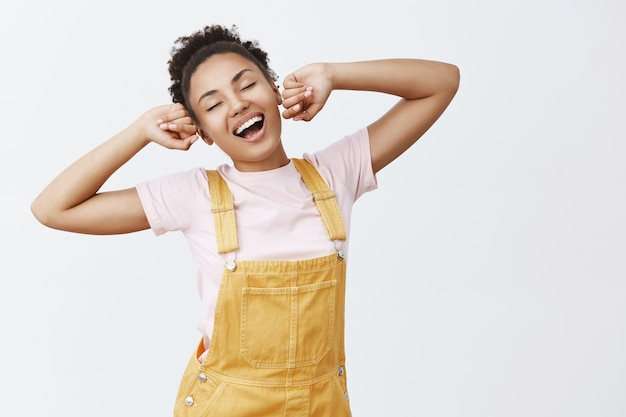 Portrait of lazy charming african american female student in stylish yellow overalls, stretching with raised hands, yawning and smiling broadly, feeling sleepy after nap