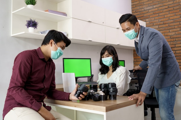 Portrait of a lens tenant. who is assisted by customer service to explain it at the work desk with mask for healthy