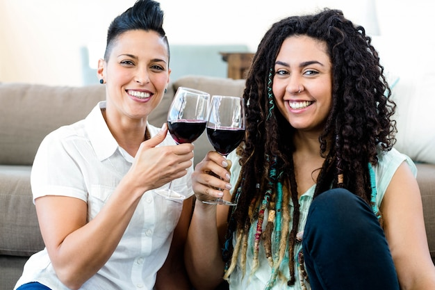 Portrait of lesbian couple smiling and toasting wine glasses