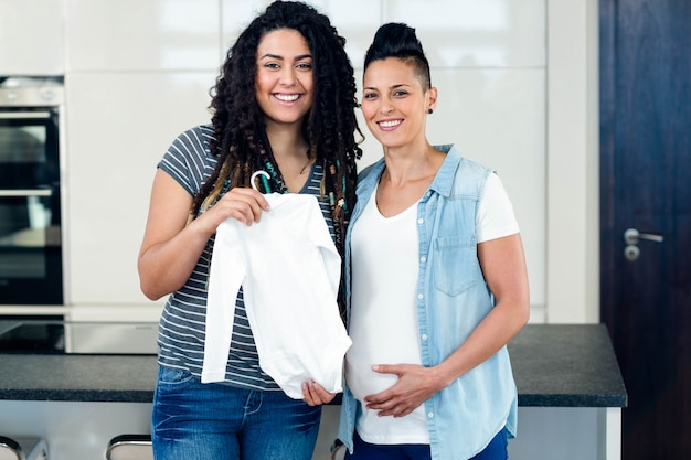 Portrait of lesbian couple standing together and holding babys clothes