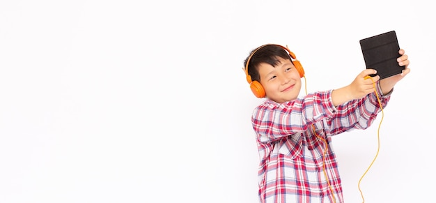 Portrait of litle boy playing at tablet and wearing headphones on white backgrond banner copy space