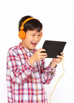 Portrait of litle boy playing at tablet and wearing headphones on white backgrond