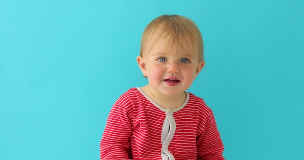 Portrait of a little 11 month old girl smiling and looking at camera on a blue background