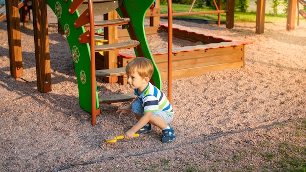 Portrait of little 3 years old toddler boy sitting on the playground and digging sand with toy plastic shovel