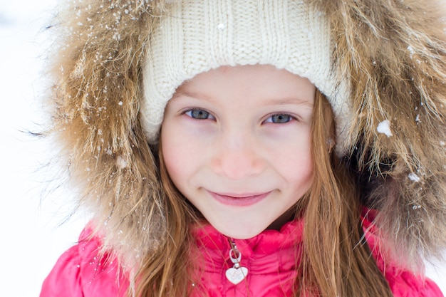Portrait of little adorable girl in snow winter day