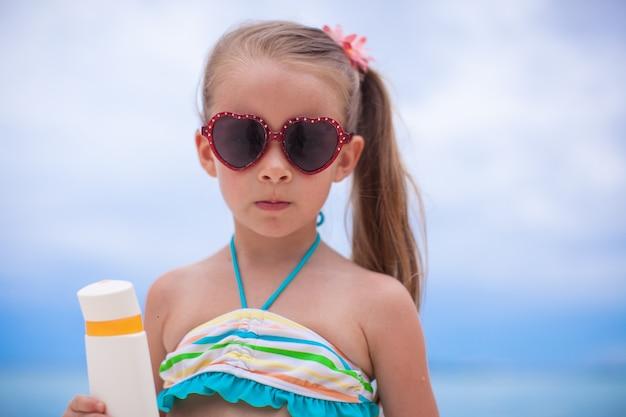 Portrait of little adorable girl in swimsuit holds suntan lotion bottle